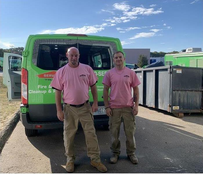SERVPRO team members, donned in pink shirts, stand by SERVPRO vehicles
